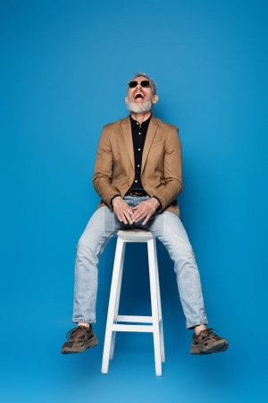 full length of middle aged man in sunglasses laughing on white chair on blue