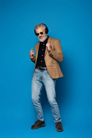 full length of pleased middle aged man in sunglasses holding smartphone and listening music in wireless headphones on blue
