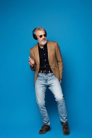 Photo pour Pleine longueur de l'homme d'âge moyen dans les lunettes de soleil tenant smartphone et écouter de la musique dans les écouteurs sur bleu - image libre de droit