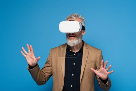 middle aged man in vr headset gesturing isolated on blue
