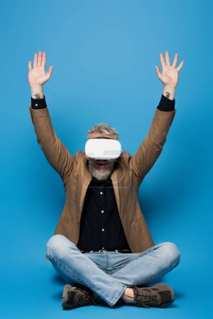 full length of excited middle aged man in vr headset sitting with crossed legs and raised arms on blue