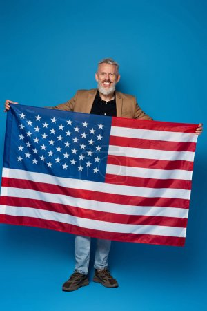 full length of happy middle aged man standing with american flag on blue