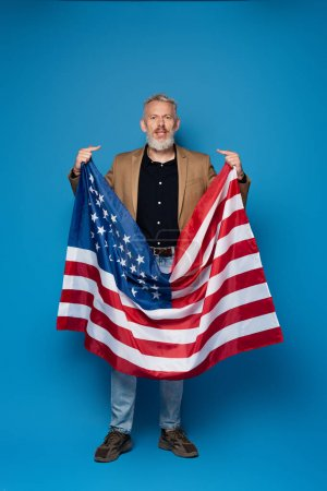 full length of bearded middle aged man standing with american flag and pointing at himself on blue
