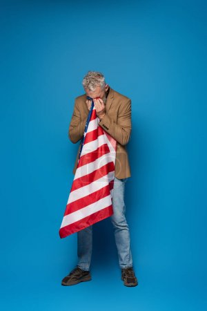 full length of patriotic middle aged man crying and covering face with american flag on blue