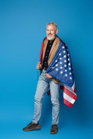 voller Länge positiver Mann mittleren Alters mit amerikanischer Flagge auf blauem Hintergrund