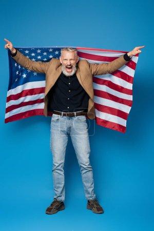 Photo pour Pleine longueur de l'homme d'âge moyen excité debout avec drapeau américain sur bleu - image libre de droit