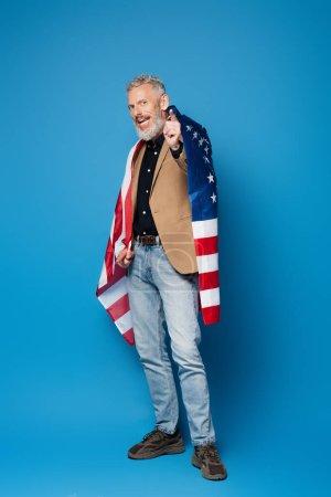 longitud completa del hombre barbudo de mediana edad de pie con bandera americana y apuntando a la cámara en azul