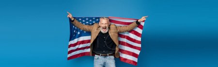 excited middle aged man standing with american flag on blue, banner