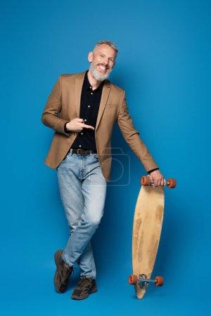 volle Länge des zufriedenen Mannes mittleren Alters zeigt auf Longboard auf blau