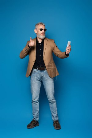 full length of middle aged man in sunglasses showing thumb up while taking selfie on blue