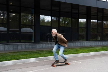 Photo for Full length of happy middle aged man in sunglasses riding longboard outside - Royalty Free Image