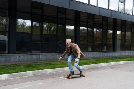 full length of positive middle aged man in sunglasses riding longboard outside