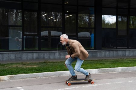 Photo for Full length of bearded middle aged man in sunglasses riding longboard outside - Royalty Free Image