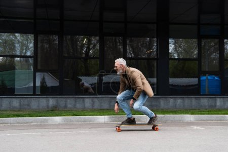 full length of middle aged man in sunglasses riding longboard near building