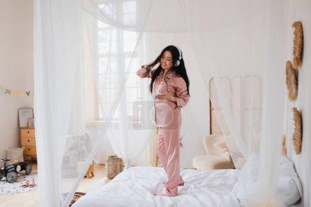 positive junge asiatische Frau tanzt auf dem Bett mit Kopfhörern und hält Handy im Schlafzimmer