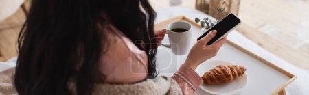 Photo pour Vue partielle de la jeune femme brune tenant un téléphone portable et prenant le petit déjeuner au lit, bannière - image libre de droit