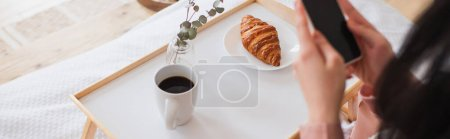 cropped view of young brunette woman holding cellphone near table with coffee and croissant in bedroom, banner