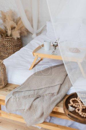 Photo pour Vue grand angle de la table avec petit déjeuner sur lit avec linge blanc dans la chambre de style bohème - image libre de droit