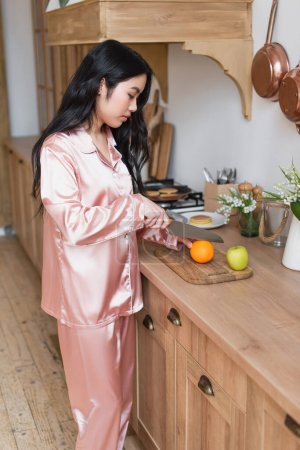Photo for Young asian woman in pink silk pajamas cutting fruits in kitchen - Royalty Free Image