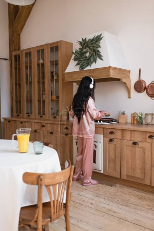 Photo for Young asian woman in pink silk pajamas and headphones cooking breakfast near table with orange juice in kitchen - Royalty Free Image
