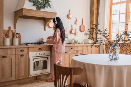 Photo for Young asian woman in pink silk pajamas and headphones cooking breakfast near table in kitchen - Royalty Free Image