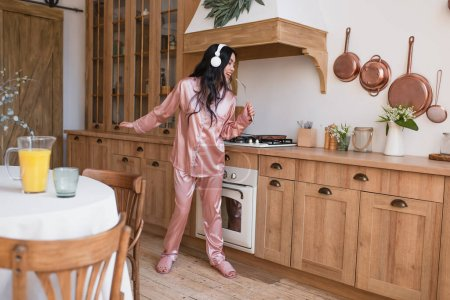 Photo for Young asian woman in pink silk pajamas and headphones cooking breakfast and singing with spatula in kitchen - Royalty Free Image