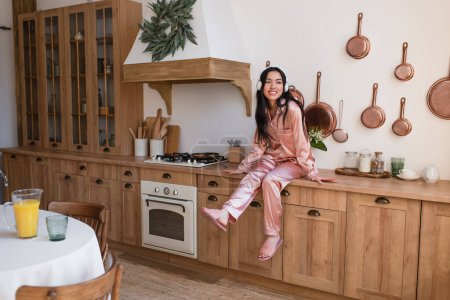 Photo for Young asian woman in pink silk pajamas and headphones sitting near stove in kitchen - Royalty Free Image