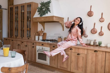 Photo for Young asian woman in pink silk pajamas and headphones sitting near stove and enjoying music in kitchen - Royalty Free Image