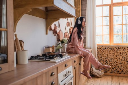 smiling young asian woman in pink silk pajamas and headphones sitting near stove and enjoying music in kitchen