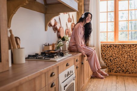 Photo for Smiling young asian woman in pink silk pajamas and headphones sitting near stove and listening music in kitchen - Royalty Free Image
