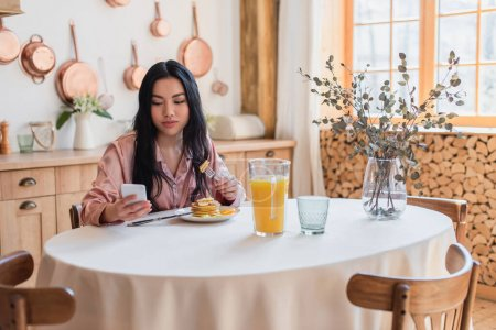 Photo for Smiling young asian woman in silk pajamas sitting on table and eating pancakes with fork while looking at cellphone in kitchen - Royalty Free Image