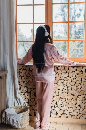 backside view of young woman standing in headphones near window at home