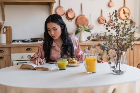 Photo for Young asian girl in silk pajamas reading book while having breakfast in kitchen - Royalty Free Image