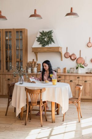 Photo for Young asian girl in silk pajamas sitting on table and reading book while having delicious breakfast in modern kitchen - Royalty Free Image