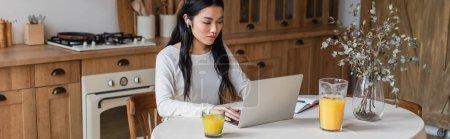 Photo pour Grave jeune asiatique femme dans écouteurs assis sur la table et en utilisant ordinateur portable près ordinateur portable avec stylo dans la cuisine, bannière - image libre de droit