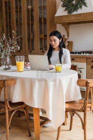 Photo pour Sérieux jeune asiatique femme dans écouteurs assis sur la table, en utilisant ordinateur portable et écriture avec stylo dans portable dans la cuisine - image libre de droit