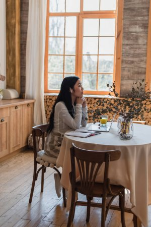 Photo for Dreamy young asian woman in casual clothes and earphones sitting on table with hands near face in kitchen - Royalty Free Image