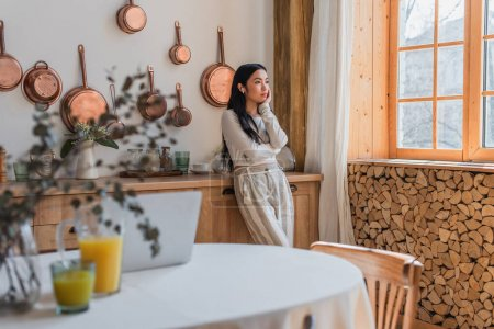 thoughtful young asian woman in blouse and trousers standing with earphones and holding hand near face in kitchen