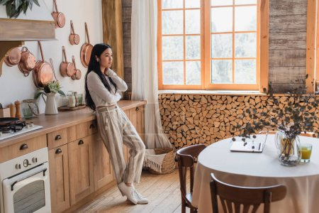Photo for Exhausted young asian woman in white casual clothes standing with earphones and holding hand near neck in kitchen - Royalty Free Image