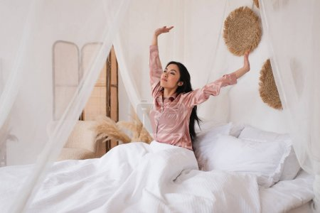 Photo pour Jeune femme asiatique en pyjama de soie se réveiller avec les mains tendues dans la chambre - image libre de droit