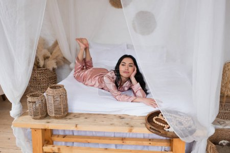 Photo for Young asian woman in silk pajamas lying with hand near face on white linen in bedroom - Royalty Free Image