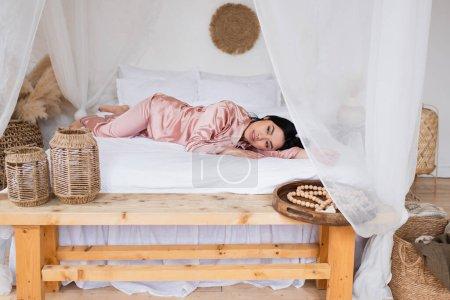 junge Asiatin im seidenen Pyjama auf weißem Leinen liegend mit ausgestreckter Hand im Schlafzimmer