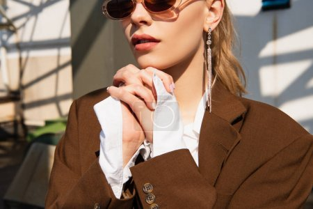 Photo for Young model with earring and sunglasses posing with clenched hands - Royalty Free Image