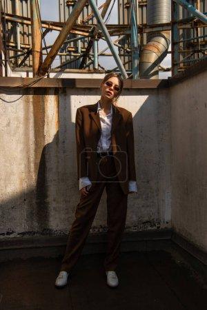 Photo pour Longueur totale de jeune modèle élégant en costume marron posant sur le toit - image libre de droit