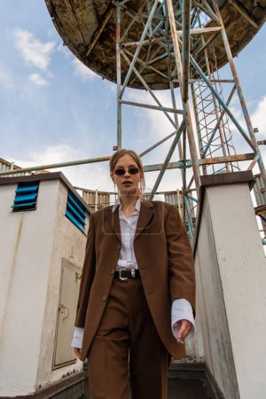 Photo for Low angle view of blonde model in sunglasses and trendy brown suit walking on rooftop - Royalty Free Image