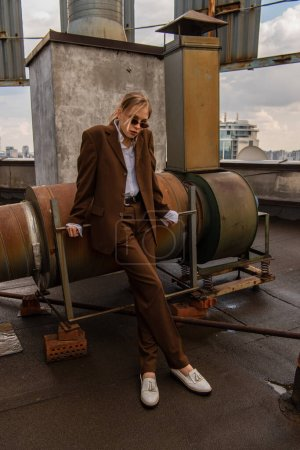 Photo for Full length of blonde model in sunglasses and trendy brown suit posing on rooftop - Royalty Free Image
