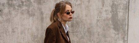 jeune modèle rêveur dans des lunettes de soleil élégantes et costume à la mode posant sur le toit, bannière
