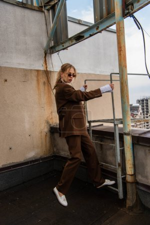 full length of young model in stylish sunglasses and trendy suit standing near metallic stairs on rooftop