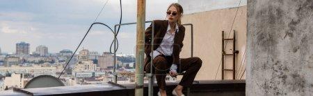 junges Model in stylischer Sonnenbrille und trendigem Anzug sitzt neben metallischen Treppen auf dem Dach, Banner