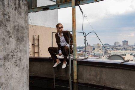 toute la longueur du jeune modèle dans des lunettes de soleil élégantes et costume tendance assis près des escaliers métalliques sur le toit